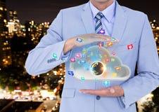 uomo d'affari con la nuvola fra le sue mani e terra sulla nuvola ed icone di applicazioni che vengono su da  Immagine Stock Libera da Diritti