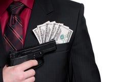 Uomo d'affari con la pistola ed i soldi. Isolato su bianco Immagini Stock
