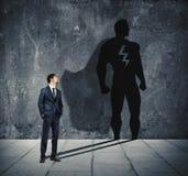 Uomo d'affari con la sua ombra dell'eroe eccellente sulla parete Concetto dell'uomo potente Fotografie Stock Libere da Diritti