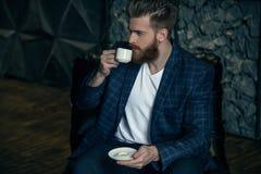 Uomo d'affari con la tazza di caffè che colloca contro del fondo moderno fotografia stock libera da diritti