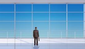 Uomo d'affari con la valigia davanti alla finestra Immagini Stock Libere da Diritti