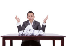 Uomo d'affari con le carte sgualcite sul suo scrittorio Fotografia Stock