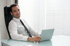 Uomo d'affari con le cuffie ed il computer portatile Fotografia Stock Libera da Diritti