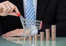 Uomo d'affari con le pile della moneta e del carrello in ufficio Immagini Stock