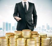 Uomo d'affari con le pile di monete di oro al fondo della città Immagini Stock