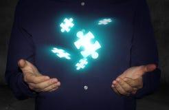 Uomo d'affari con levitare i pezzi di puzzle Fotografia Stock Libera da Diritti