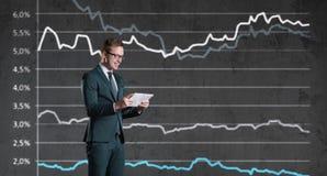 Uomo d'affari con lo smartphone che sta su un fondo del diagramma Bu Immagine Stock