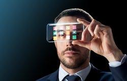 Uomo d'affari con lo smartphone trasparente Fotografia Stock