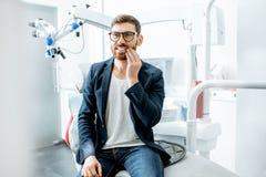Uomo d'affari con mal di denti nell'ufficio dentario fotografia stock