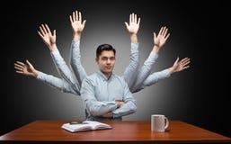 Uomo d'affari con molte mani dietro immagine stock libera da diritti