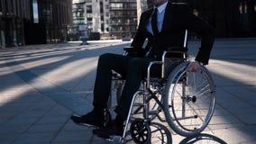 Uomo d'affari con nella sedia a rotelle che si gira intorno verso la macchina fotografica con il sorriso felice stock footage