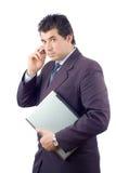 Uomo d'affari con un computer portatile che comunica su un telefono delle cellule Fotografia Stock