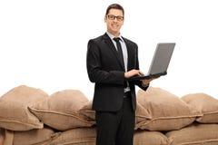 Uomo d'affari con un computer portatile davanti ad un mucchio dei sacchi della tela da imballaggio Fotografia Stock