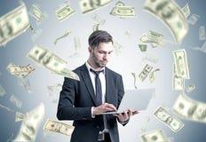 Uomo d'affari con un computer portatile sotto la pioggia del dollaro Fotografia Stock