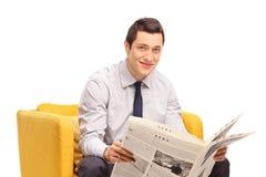 Uomo d'affari con un giornale che si siede in una poltrona gialla immagine stock