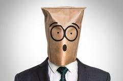 Uomo d'affari con una borsa sul capo- con il fronte sorpreso immagini stock libere da diritti