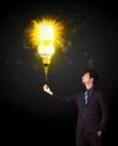 Uomo d'affari con una lampadina ecologica Immagini Stock Libere da Diritti