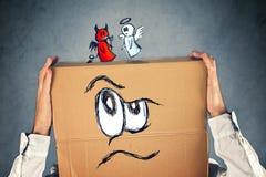Uomo d'affari con una scatola di cartone e un angelo e diavolo sulla sua testa immagine stock