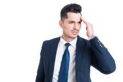 Uomo d'affari concentrato e sollecitato che ha un'emicrania immagine stock