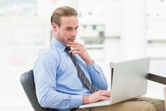 Uomo d'affari concentrato facendo uso del computer portatile fotografie stock libere da diritti