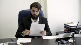 Uomo d'affari concentrato, serio, giovane, barbuto che si siede in poltrona di cuoio blu nell'ufficio e che legge le carte video d archivio