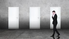 Uomo d'affari confuso che sceglie la porta giusta archivi video