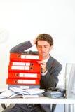 Uomo d'affari confuso che si siede allo scrittorio con i dispositivi di piegatura Fotografia Stock Libera da Diritti