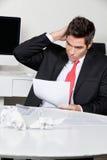 Uomo d'affari confuso Working At Desk Fotografie Stock