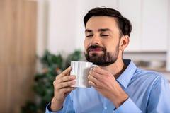 Uomo d'affari contentissimo che odora il suo caffè immagini stock libere da diritti