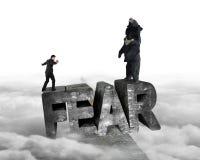 Uomo d'affari contro l'orso che equilibra sulla parola di timore 3D con nuvoloso Immagini Stock Libere da Diritti