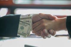 Uomo d'affari corrotto che sigilla l'affare con una stretta di mano e che riceve i soldi del dono, un'anti corruzione ed i concet immagine stock
