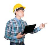Uomo d'affari costruendo il punto usando sicuro del computer portatile e della mano del computer indossi la plastica gialla del c immagine stock libera da diritti