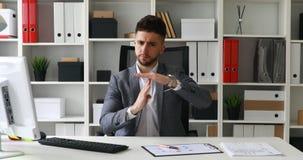 Uomo d'affari in costume che si siede alla tavola in ufficio bianco e che esamina macchina fotografica