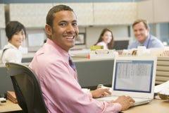 Uomo d'affari in cubicolo usando computer portatile e sorridere Immagine Stock