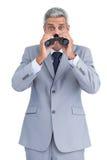 Uomo d'affari curioso osservando con il binocolo Fotografia Stock