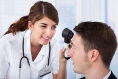 Uomo d'affari d'esame di medico con dermoscope Fotografia Stock Libera da Diritti