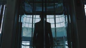 Uomo d'affari da un elevatore di vetro archivi video