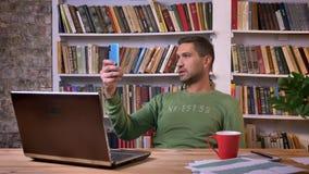 Uomo d'affari davanti al computer portatile che ha una video chiamata sul telefono, girante intorno sulla sedia Scaffali per libr archivi video