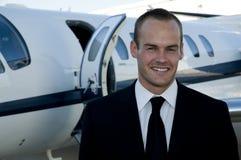 Uomo d'affari davanti al jet corporativo Fotografia Stock