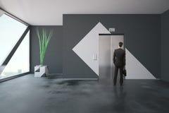 Uomo d'affari davanti all'elevatore Immagine Stock