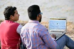 Uomo d'affari dei giovani due facendo uso del computer portatile in all'aperto fotografie stock