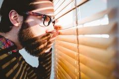 Uomo d'affari dei pantaloni a vita bassa che dà una occhiata attraverso i ciechi immagini stock libere da diritti