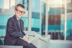Uomo d'affari del bambino con il computer portatile Immagini Stock