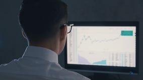 Uomo d'affari del finanziere negli impianti di vetro sul mercato finanziario sul computer alla notte stock footage