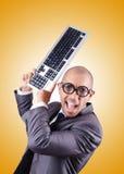 Uomo d'affari del nerd con la tastiera di computer contro Fotografia Stock Libera da Diritti