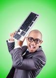 Uomo d'affari del nerd con la tastiera di computer contro Fotografia Stock