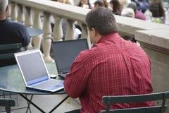 Uomo d'affari del pranzo dei due computer portatili Fotografia Stock Libera da Diritti