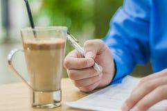 Uomo d'affari del primo piano che si siede alla tavola in ufficio interno ed attentamente che scrive alcune note Caffè sulla tabe Fotografie Stock Libere da Diritti