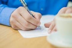 Uomo d'affari del primo piano che si siede alla tavola in ufficio interno ed attentamente che scrive alcune note Caffè sulla tabe Immagine Stock