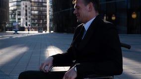 Uomo d'affari del ritratto con girarsi intorno verso la macchina fotografica sulla sedia a rotelle con il sorriso felice video d archivio